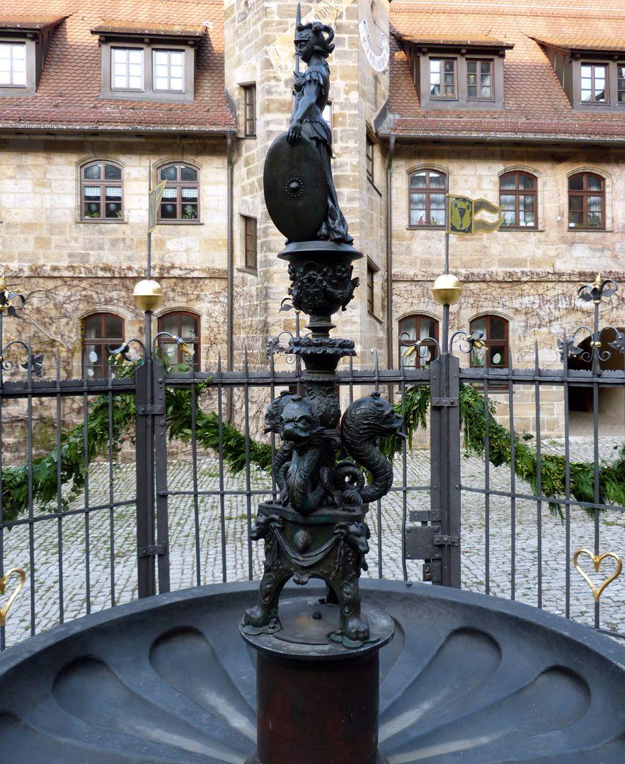 Athene-Brunnen linkes Profil der Figurine über dem Brunnenpfosten, antikisierender Dreifuß mit drei wasserspeienden Meereswesen, darüber vasenförmige Konsole