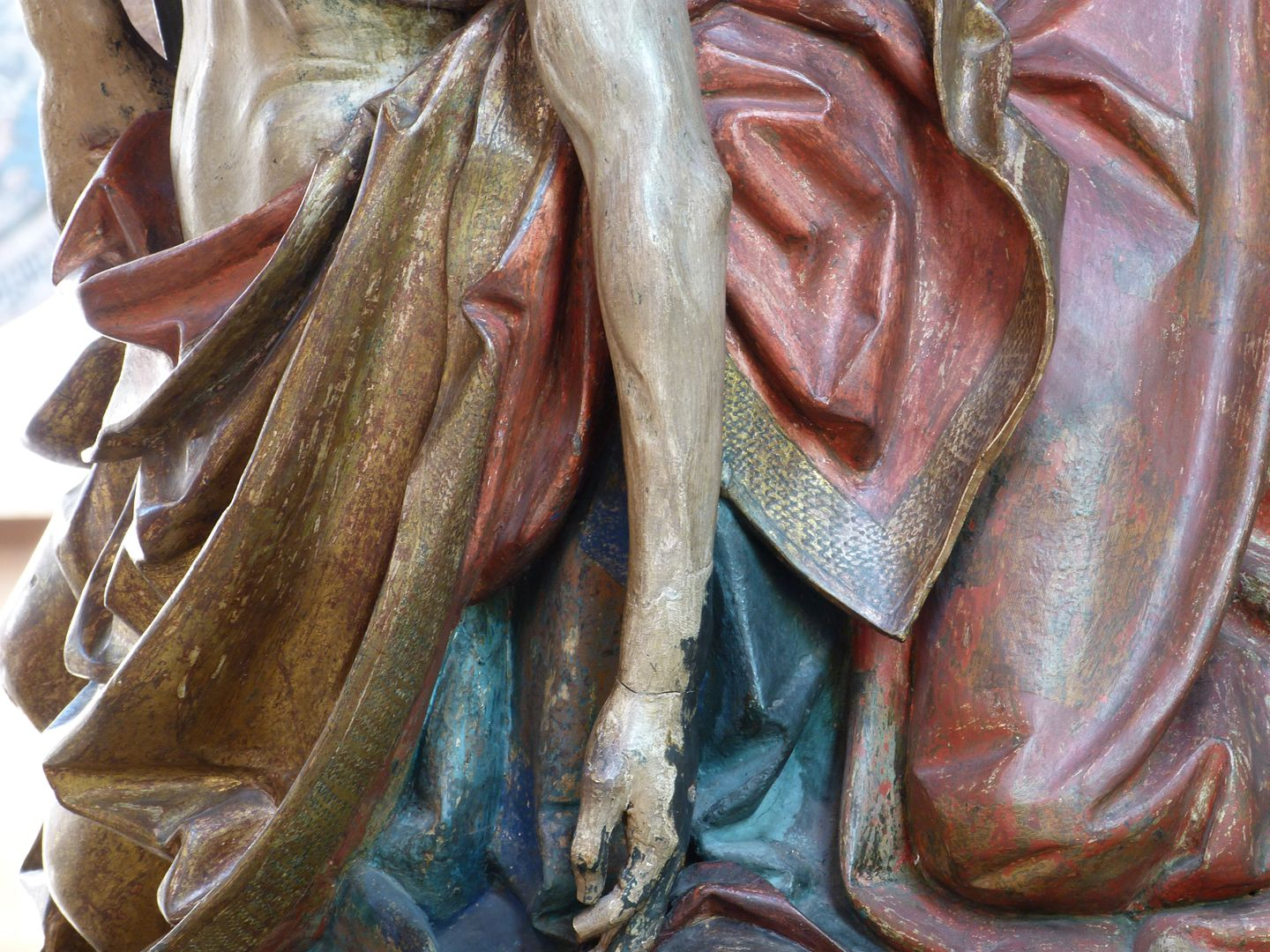 Great Pietà Jesus' body wrapped in Mary's golden cloak, Mary's blue robe and John's red robe.