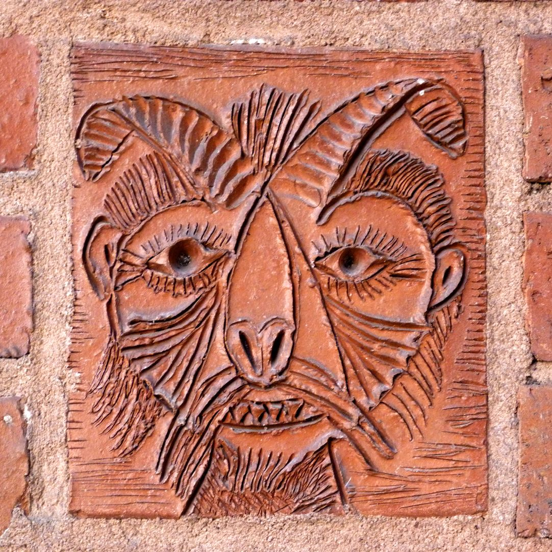 Residential- and business building Detail of the ceramic relief with faun head