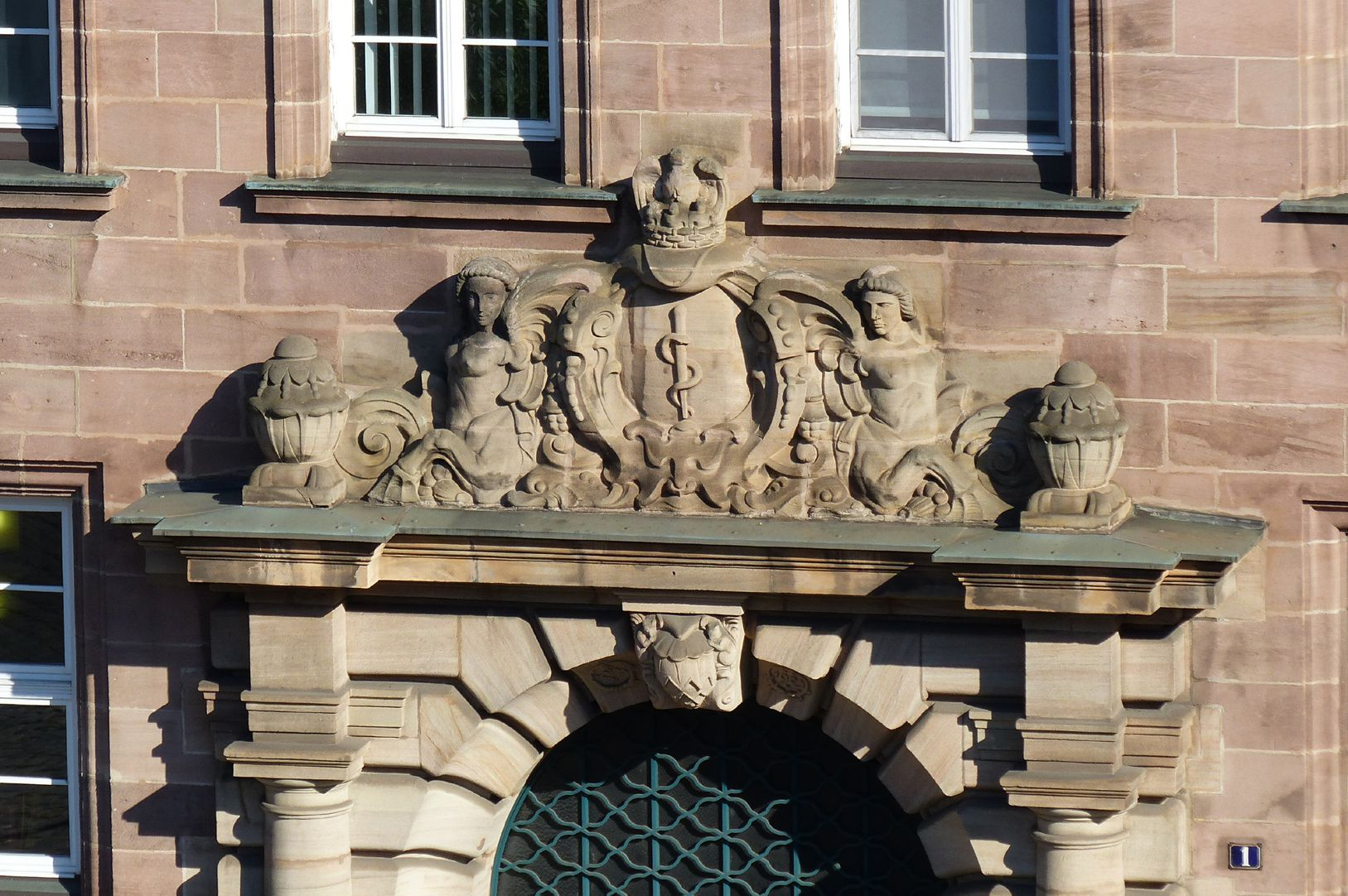 Former General Health Insurance Crowning structure of the main portal with the Aesculapian coat of arms