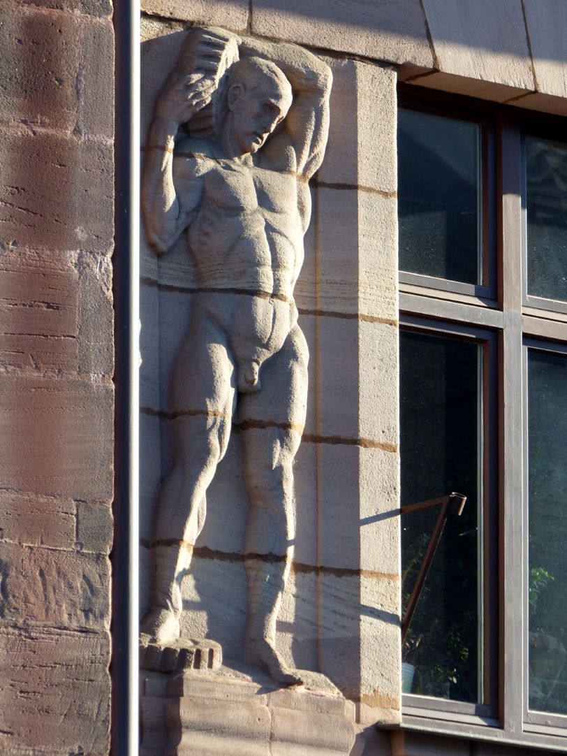 Business- and office building, Hefnersplatz 7 Worker with two cogwheels on fourth storey