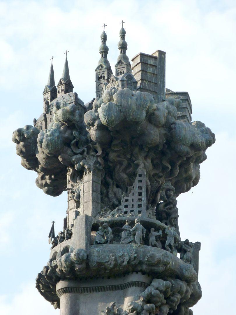 History Column Spitze der Historiensäule: nach den verheerenden Zerstörungen des Zweiten Weltkrieges bildet die wiederaufgebaute Stadt die Bekrönung. (oben: Florinskirche mit Florinsmarkt, Frauenkirche und Zentralplatz)