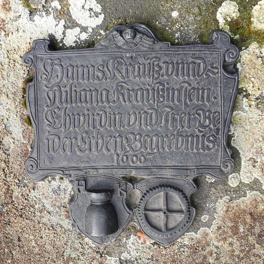 """Johann Pachelbel Gravesite Commemorative plaque Location in the burial ground Epitaph: """"Hanns Krauß and Juliana Kraußin his wife´s and both of their heirs´gravesite in 1600"""" / On the lower left a tied flour sack with the letters H and K, on the right a gear wheel with 45 teeth. His"""