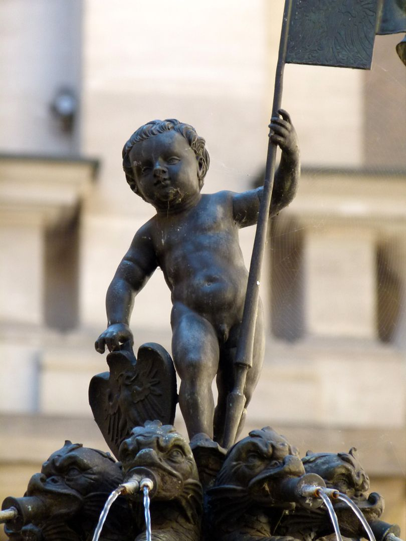 Putto-Fountain Putto of 1557 as bearer of the flag and the Nuremberg coat of arms standing on the eight dragon gargoyles