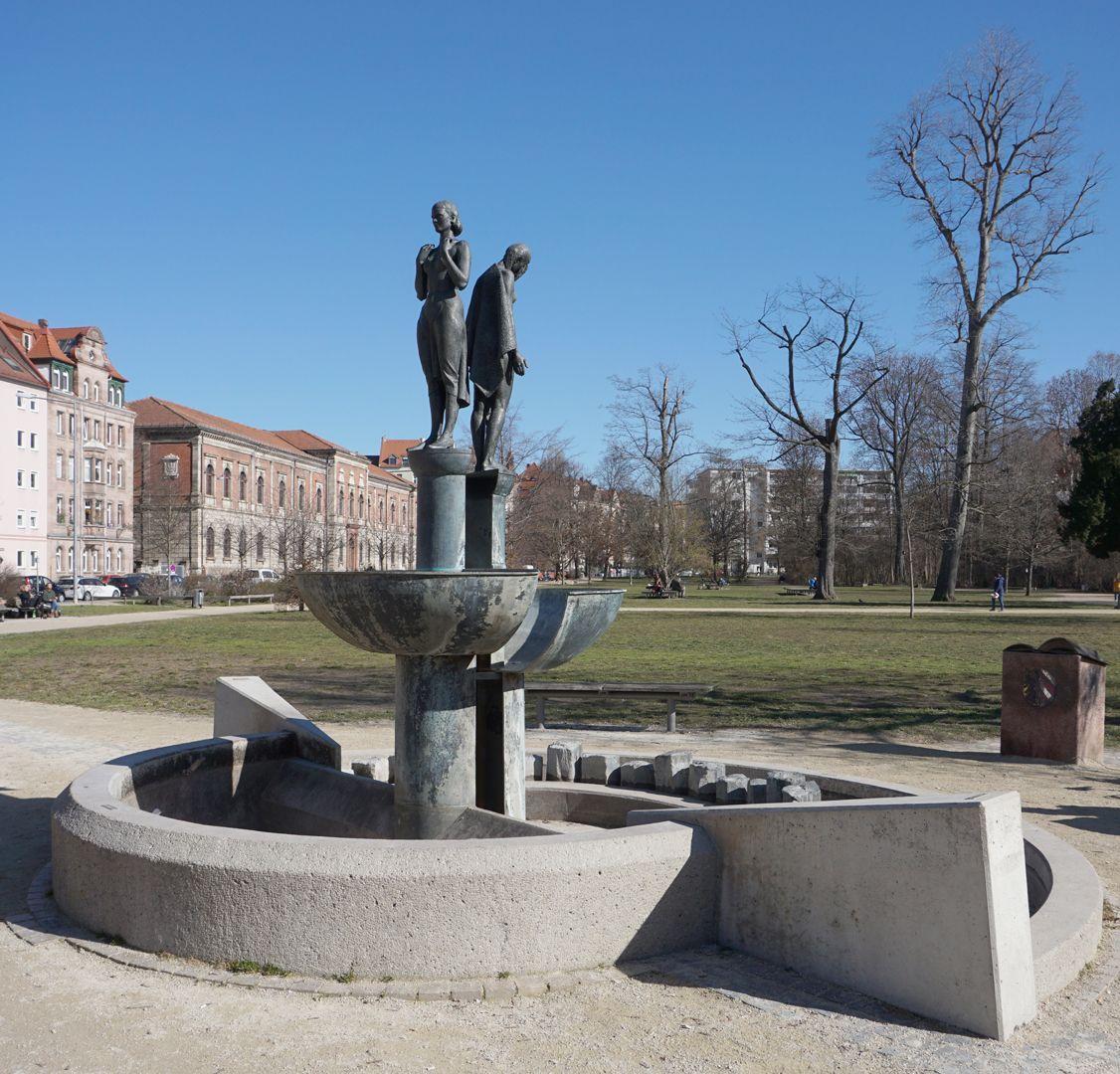 Norisbrunnen Zweigeteilte Brunnenanlage. Obere Brunnenschale mit aufrecht stehender Frauengestalt. Untere offene Brunnenschale mit gebeugter entblößter Frauengestalt.