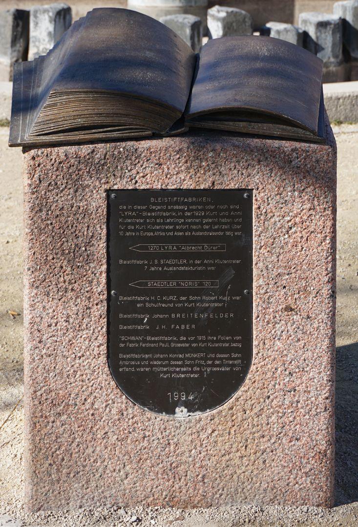 Norisbrunnen Aus der Bindung gehendes bronzenes Buch mit Stifterwidmung auf einem Steinpult mit Informationstafel